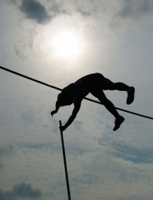 Raising the bar: An athlete pole vaults over a bar, silhouetted against the sun