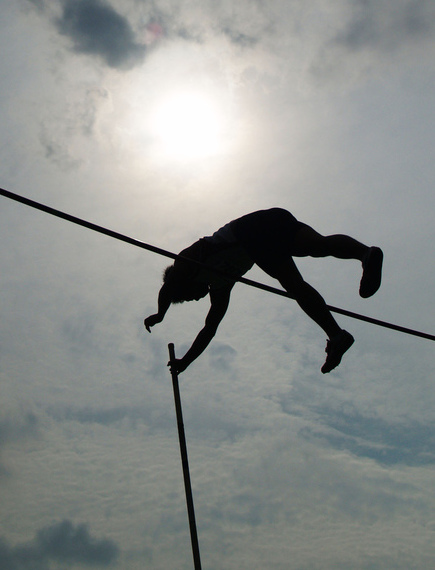 A pole vaulter, silhouetted against the sun, vaults over a high bar